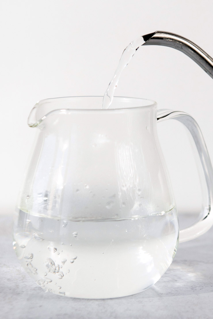 Pouring hot water into a glass teapot.