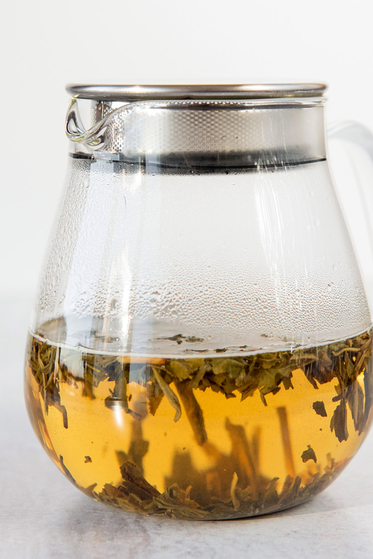 Loose tea steeping in a covered glass teapot.