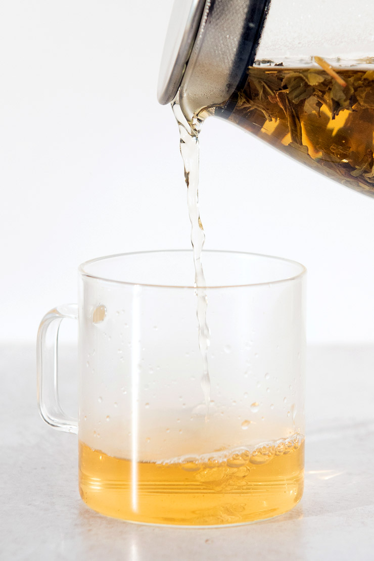 Pouring hot jasmine tea into a glass mug from a teapot.