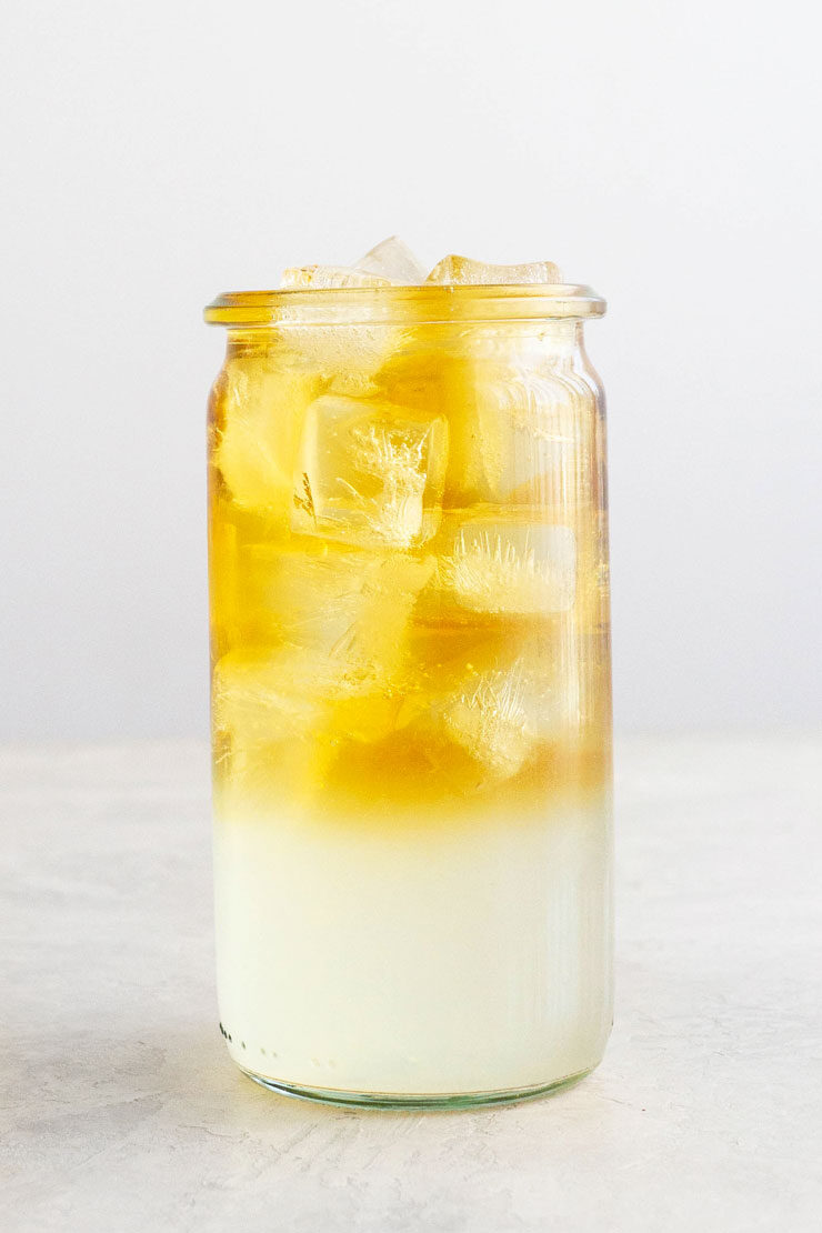 Layered Arnold Palmer drink with lemonade and iced tea in a cup with ice