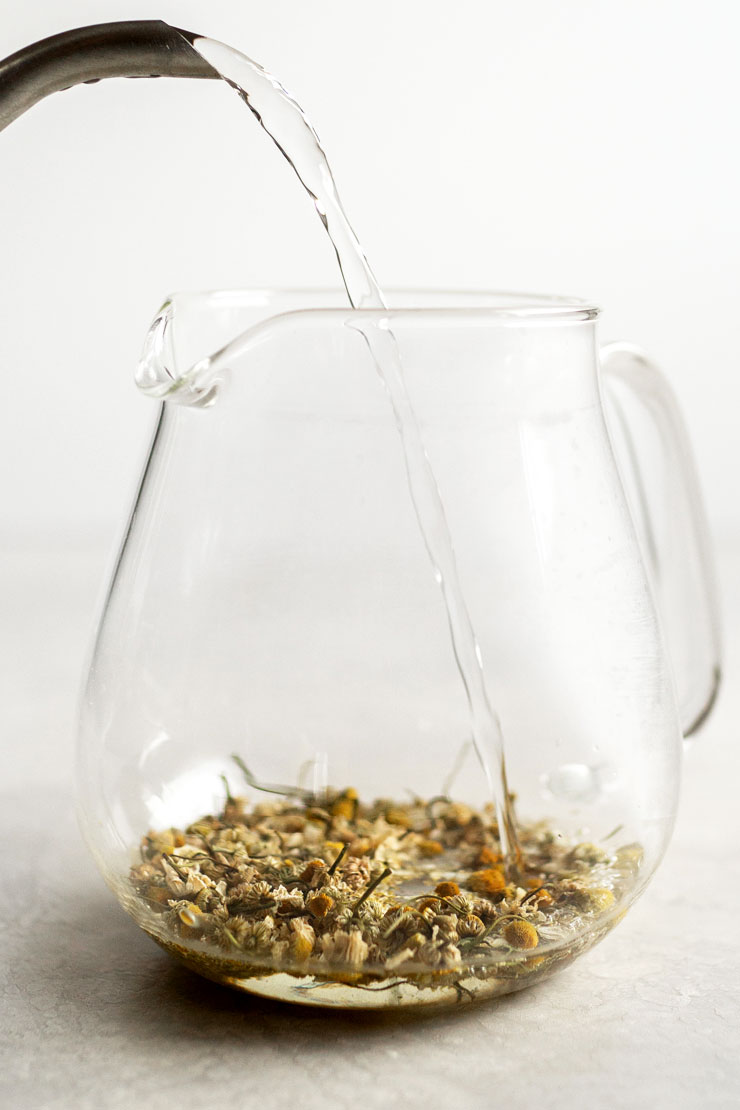 Hot water into a teapot with chamomile tea