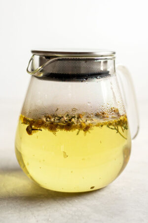 Chamomile tea in a glass teapot.