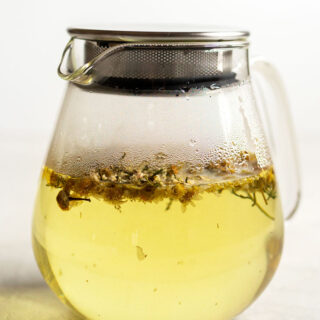 Chamomile tea in a glass teapot.