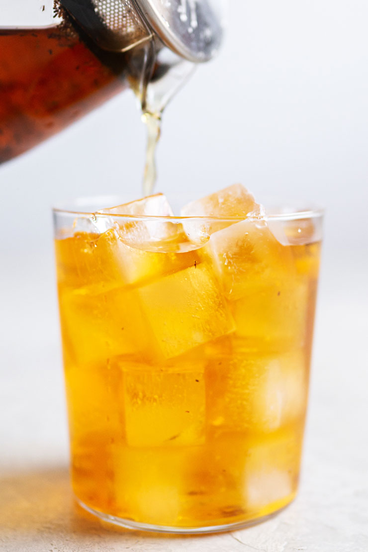 Pouring iced rooibos tea into a cup with ice.