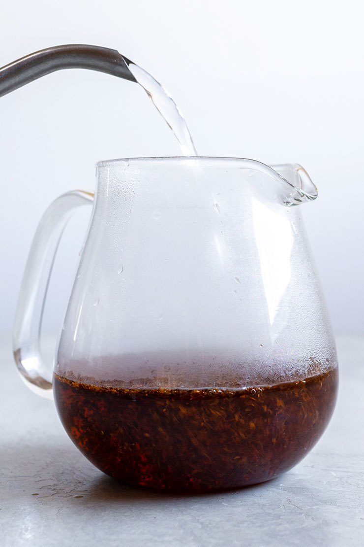 Pouring hot water into a glass teapot with rooibos loose tea.