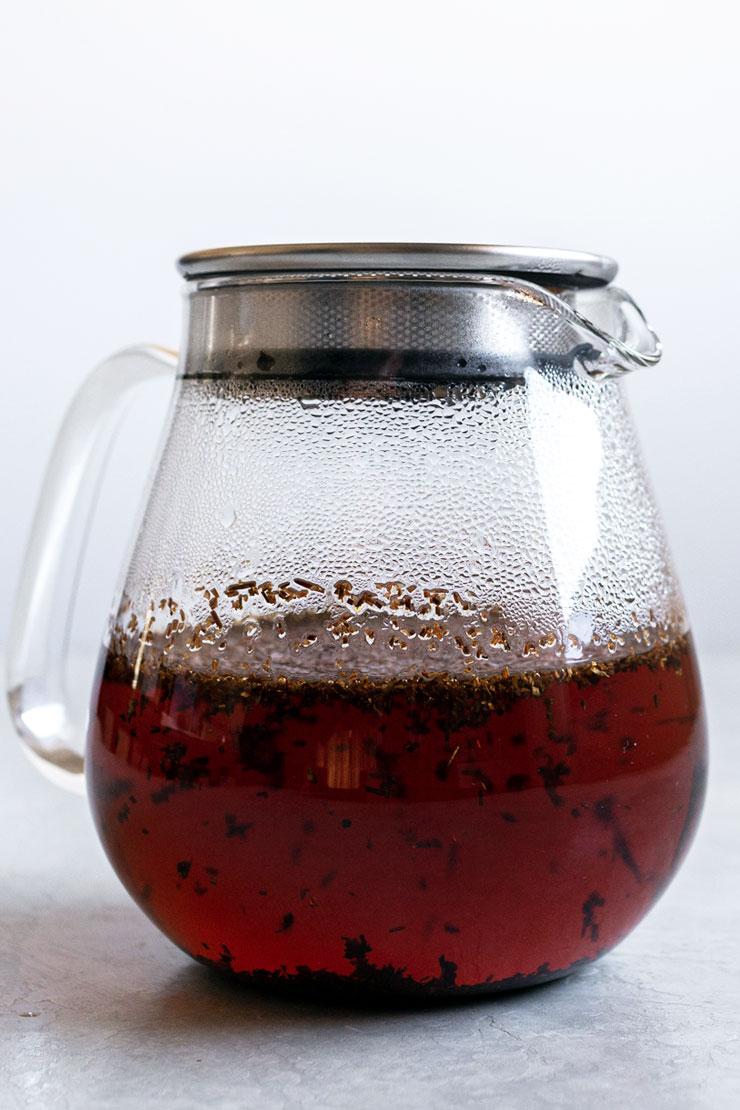 Rooibos loose tea steeping in hot water in a glass teapot.