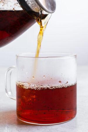 Pouring rooibos tea into a glass mug.