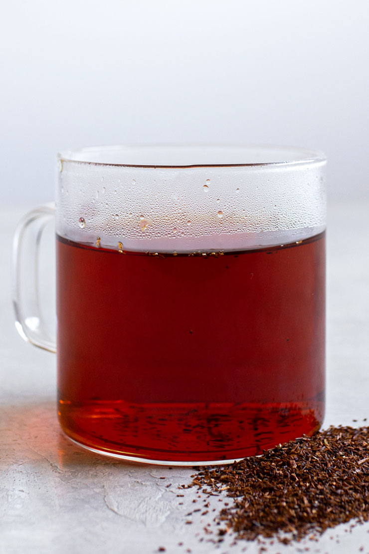 Hot rooibos tea in a glass mug.