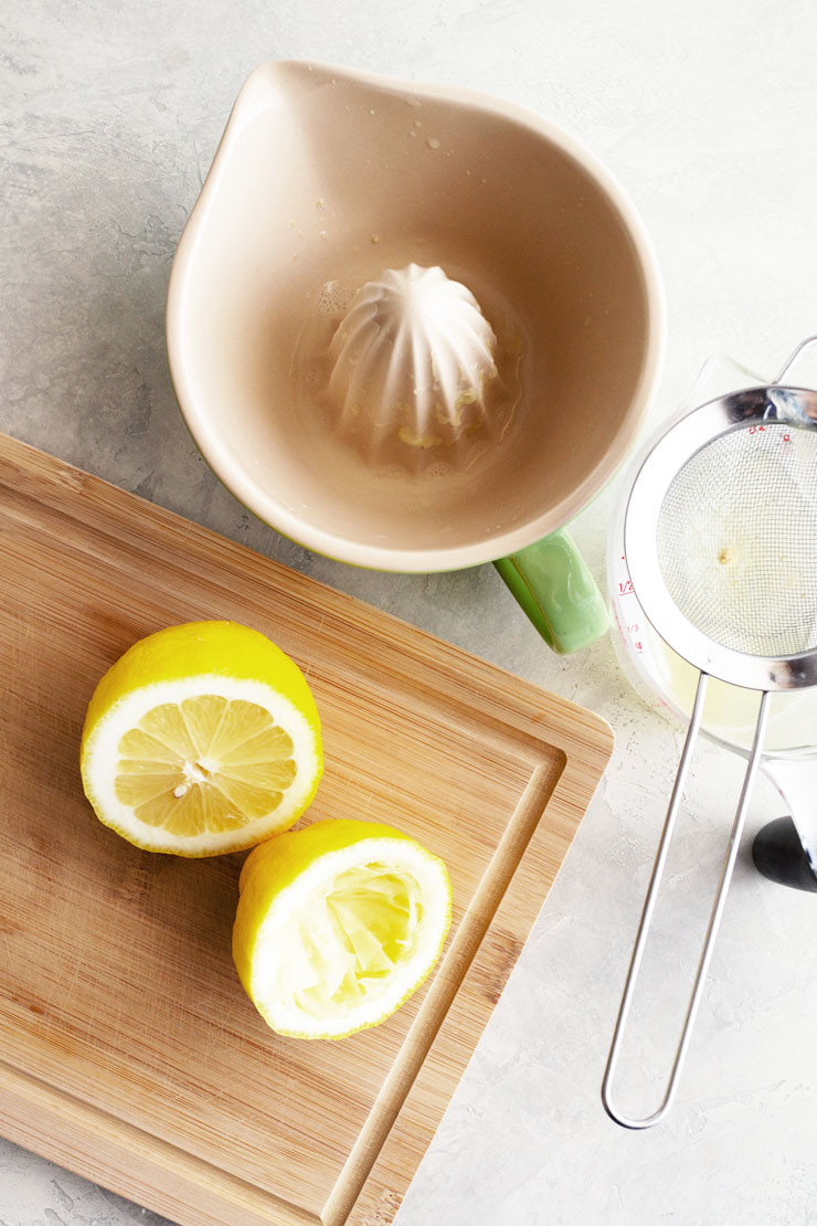 Fresh lemons cut on a cutting board with citrus juicer