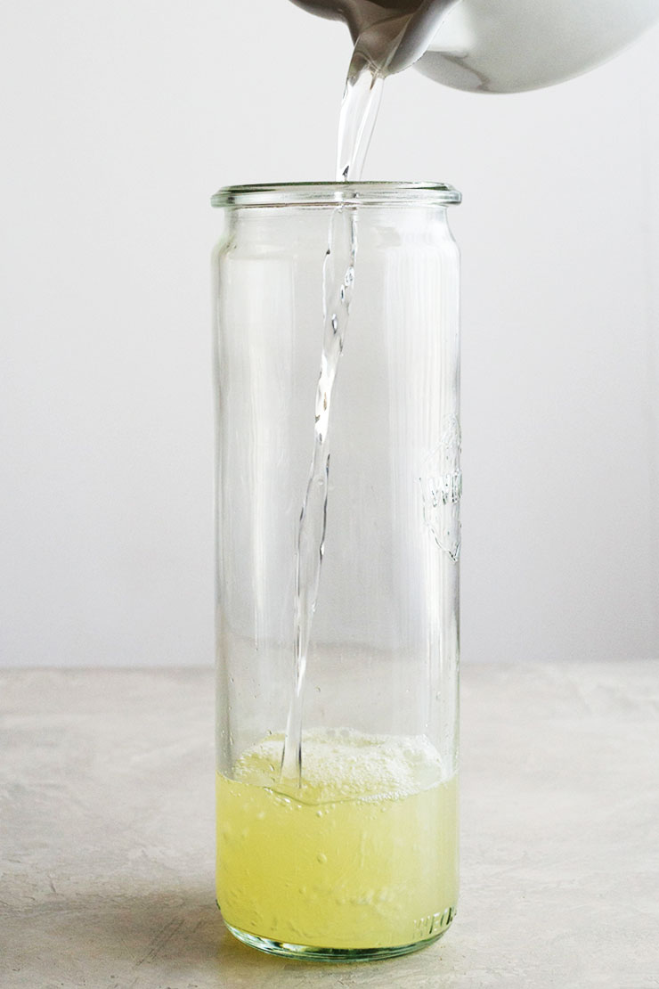 Pouring simple syrup into lemon juice in a tall jar