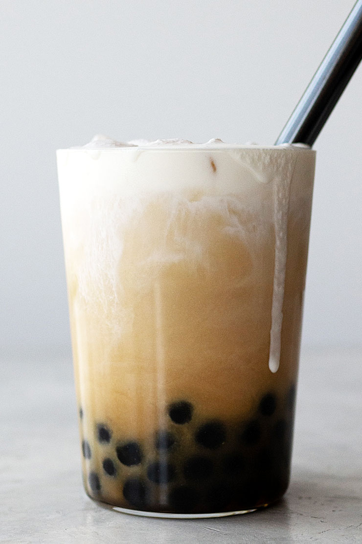 Bubble tea in tall glass cup with black straw.