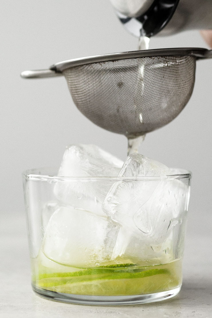 straining yerba mate into a cup with ice