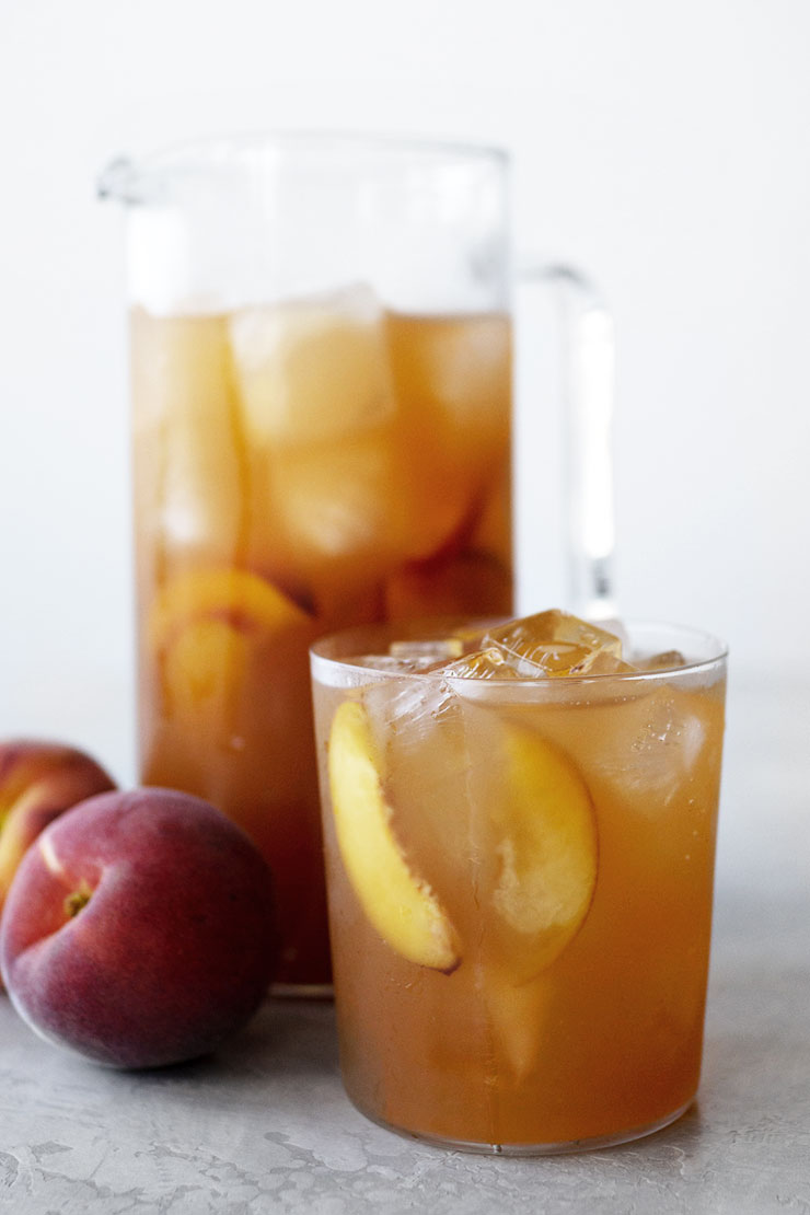 Peach iced tea in glass and pitcher