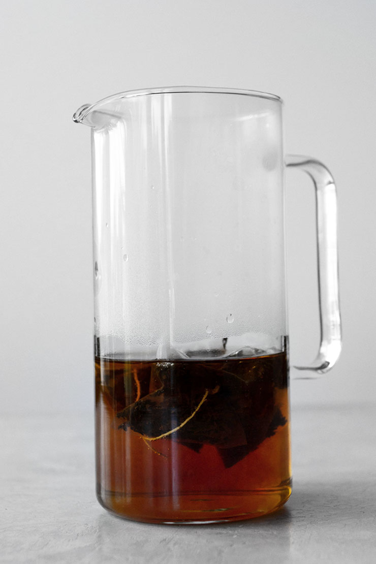 Tea sachets steeping in glass pitcher.