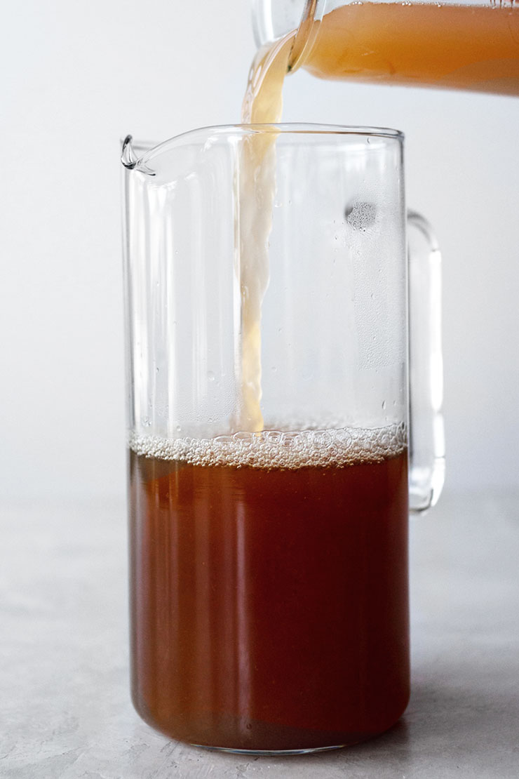 combining tea and peach simple syrup in a pitcher