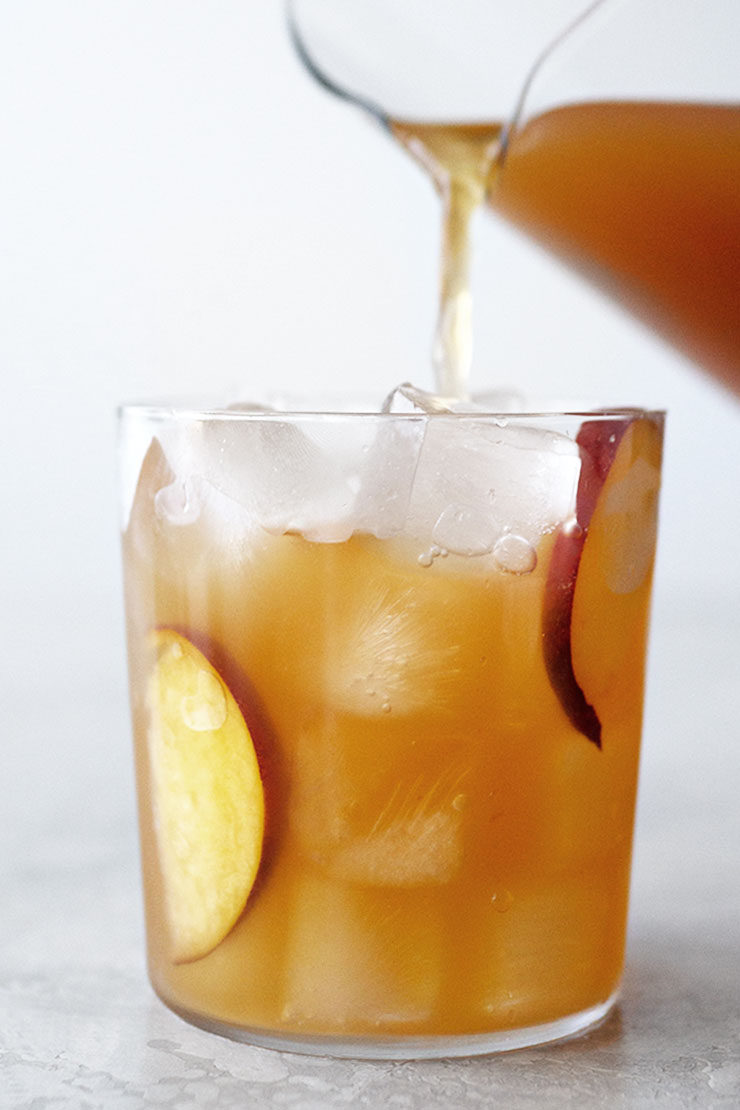 pouring peach iced tea into a glass with ice