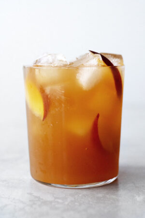 Peach iced tea in a glass with peach slices.