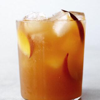 Peach iced tea in a glass with peach slices.