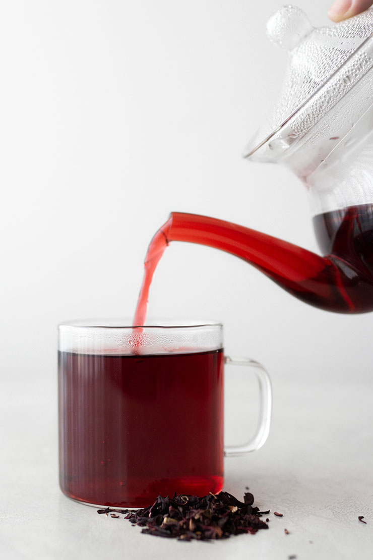 Pouring hibiscus tea into a clear mug