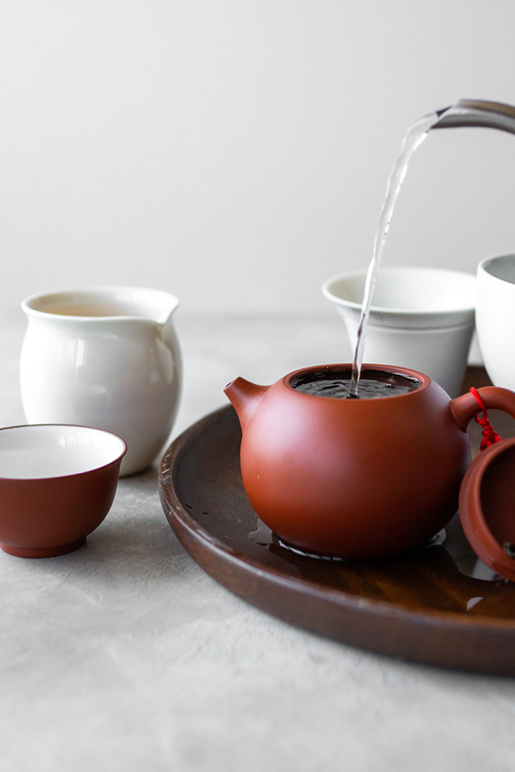 Pouring hot water into clay teapot