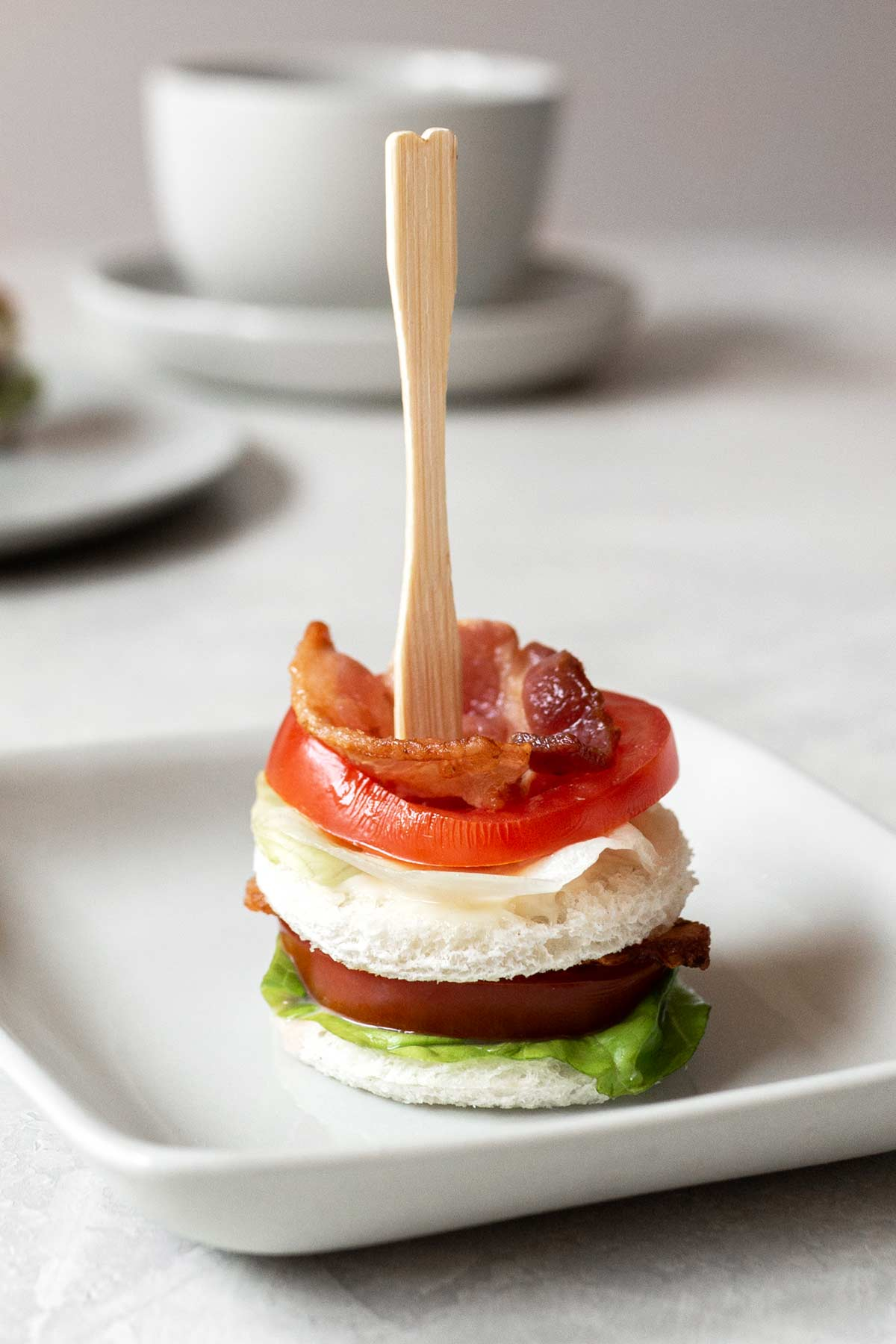 BLT tea sandwich with a cocktail fork on a small plate.