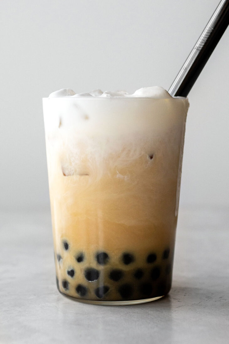 Bubble tea in a glass cup with a black straw.