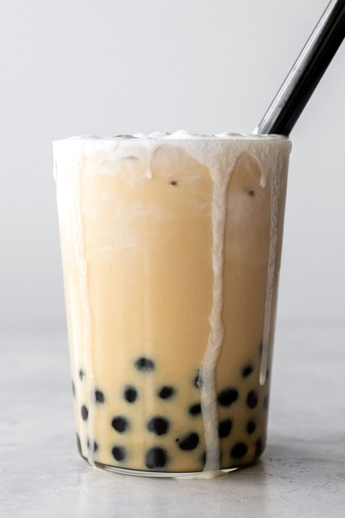 Milk tea with tapioca balls in a tall glass with black straw.