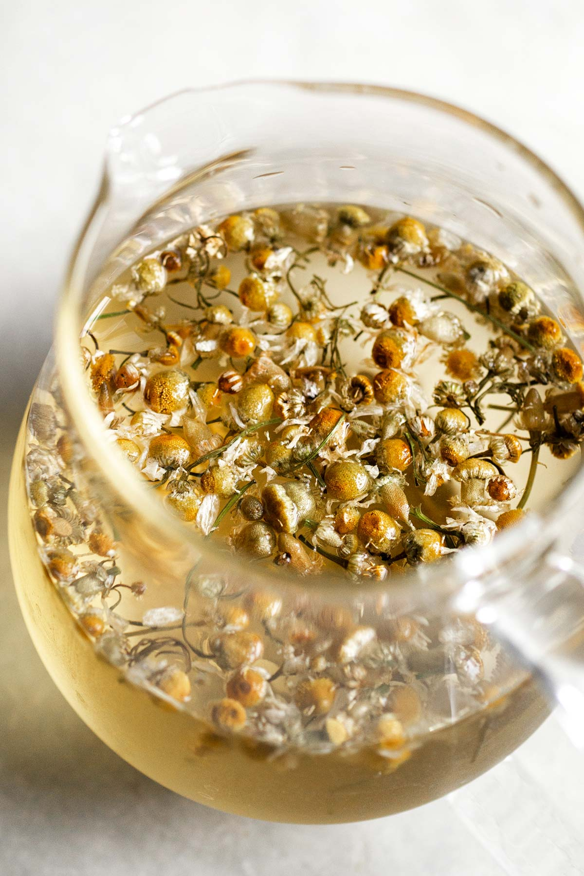 Steeping chamomile flowers in a teapot with hot water.