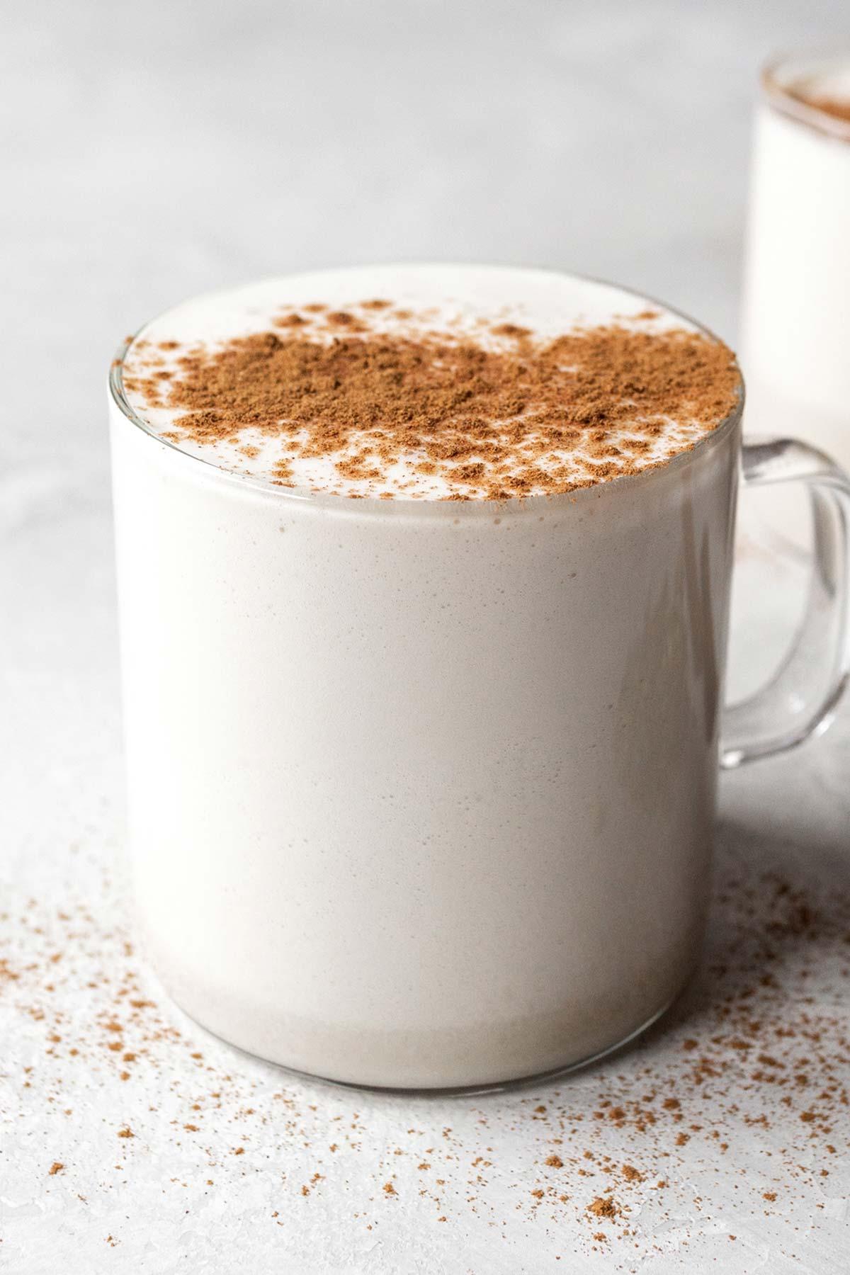 Chamomile tea latte with ground cinnamon garnish in a glass mug.