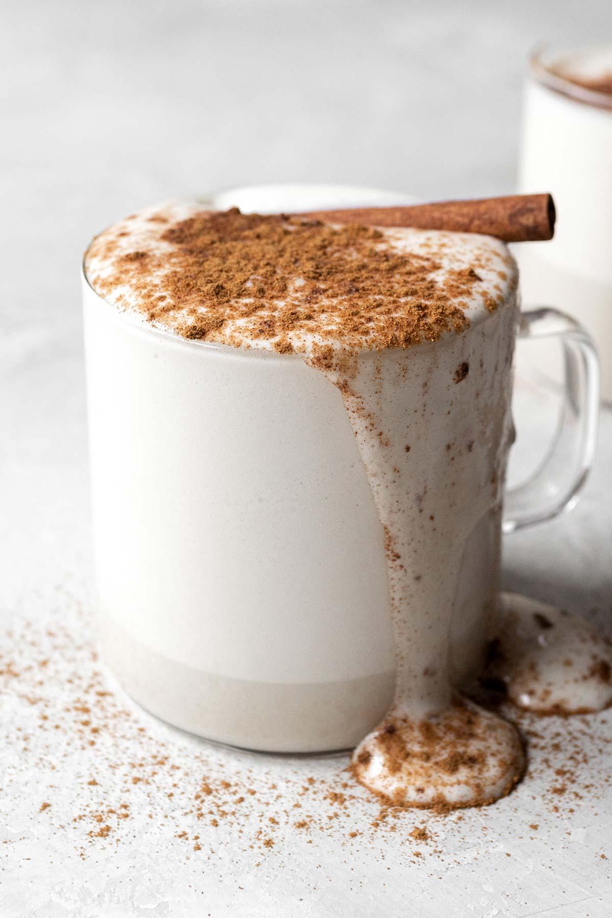 Chamomile tea latte garnished with ground cinnamon and a cinnamon stick in a glass mug.