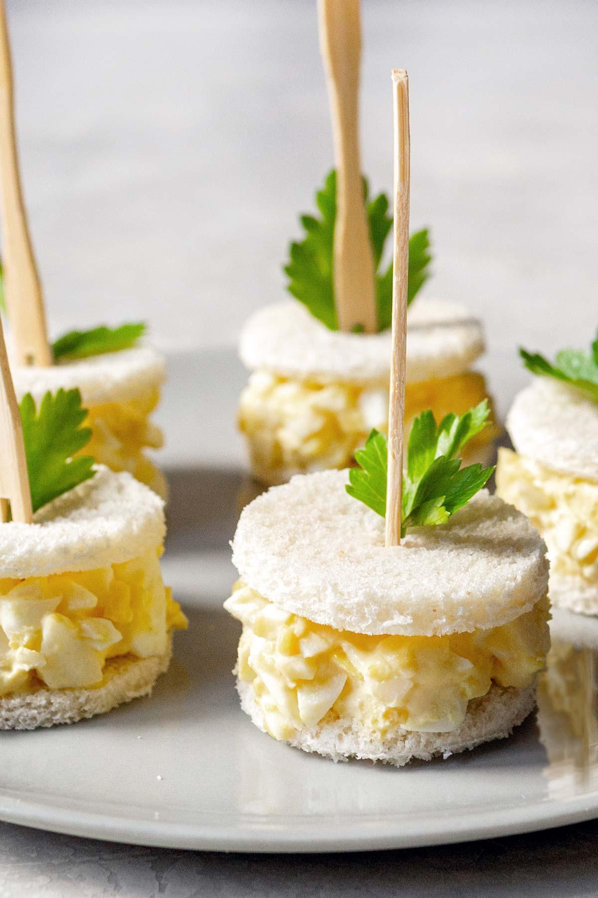 Egg salad tea sandwiches on a plate.