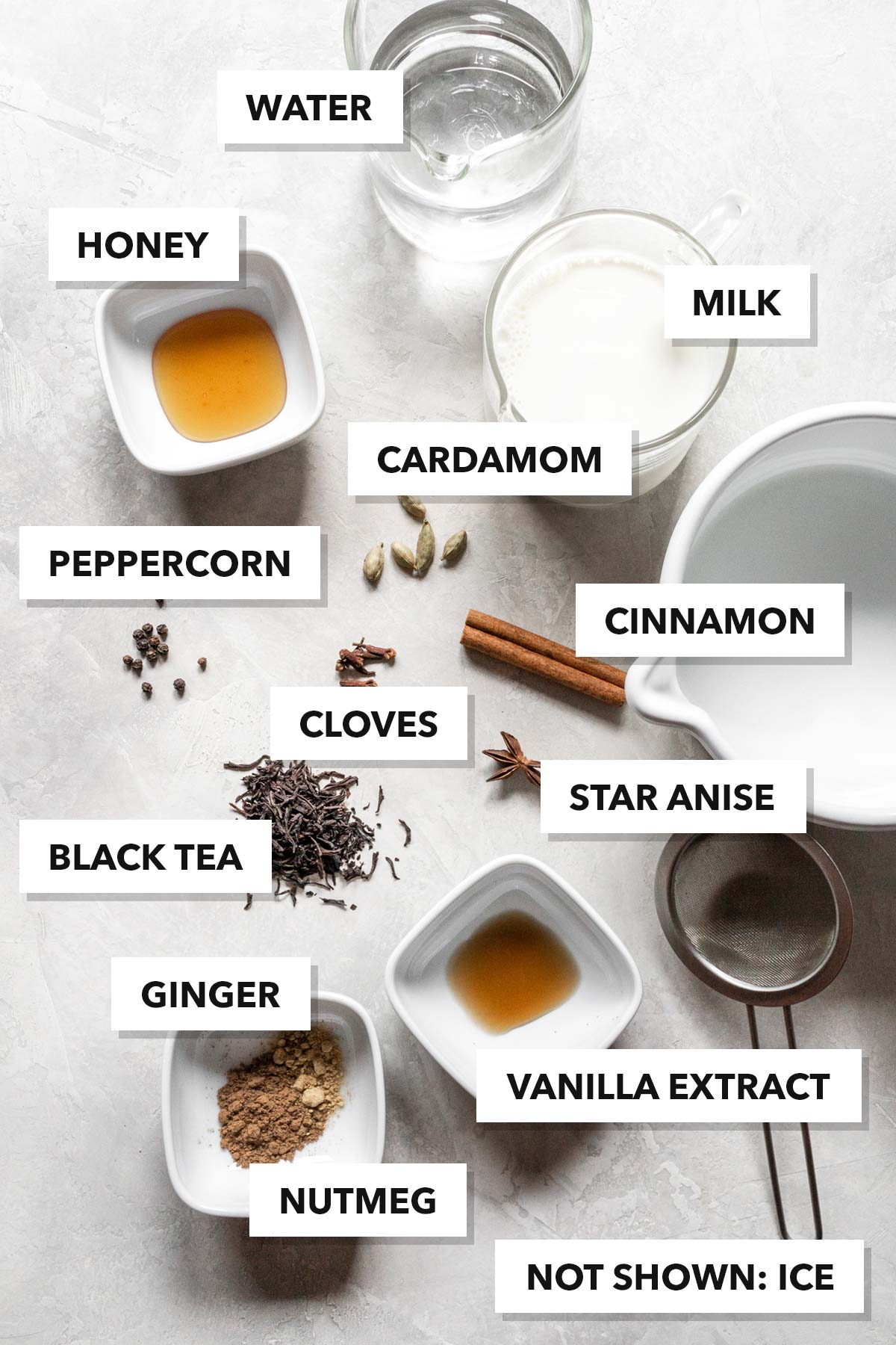Ingredients to make a chai latte on a surface and each item labeled with the name.