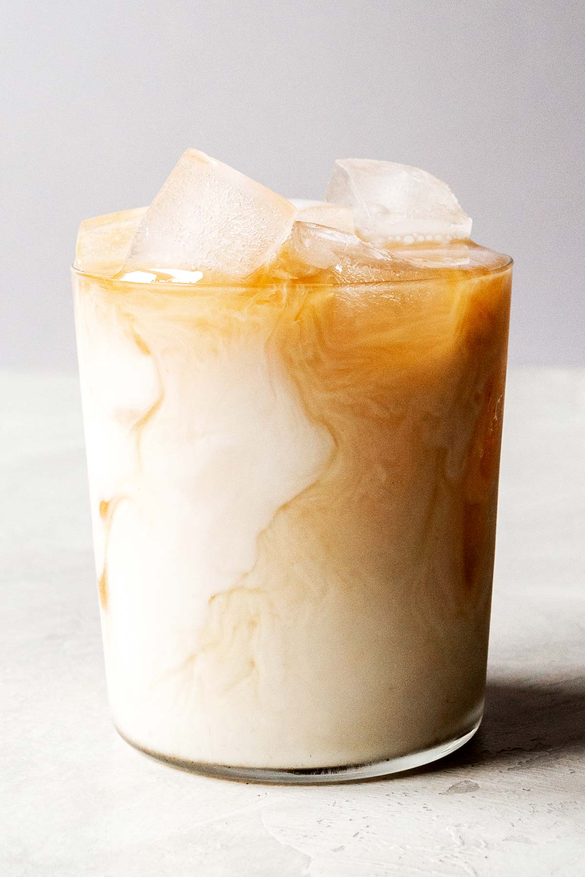 Iced chai latte in a glass with swirls of milk.