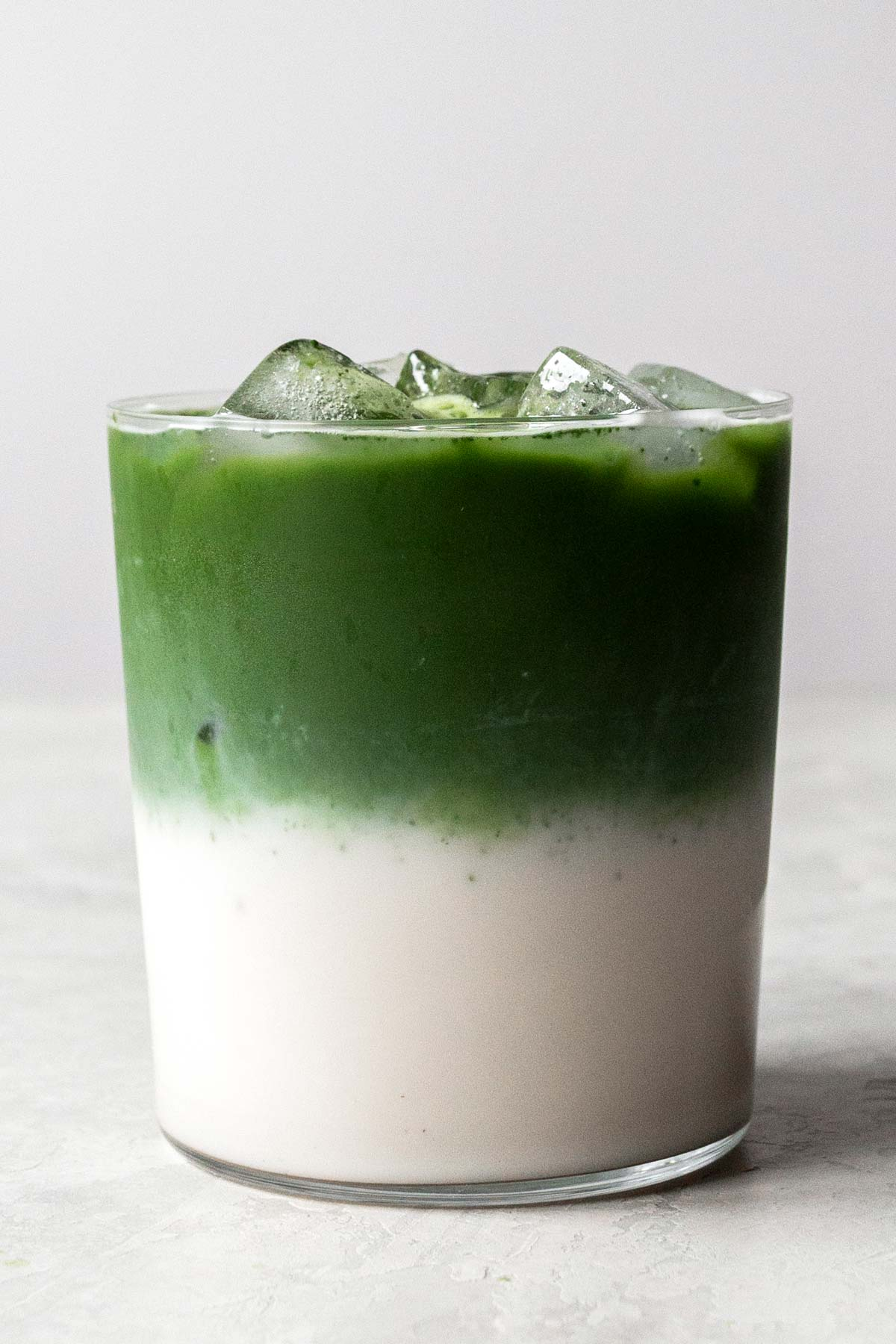 Layered iced matcha latte in a cup.