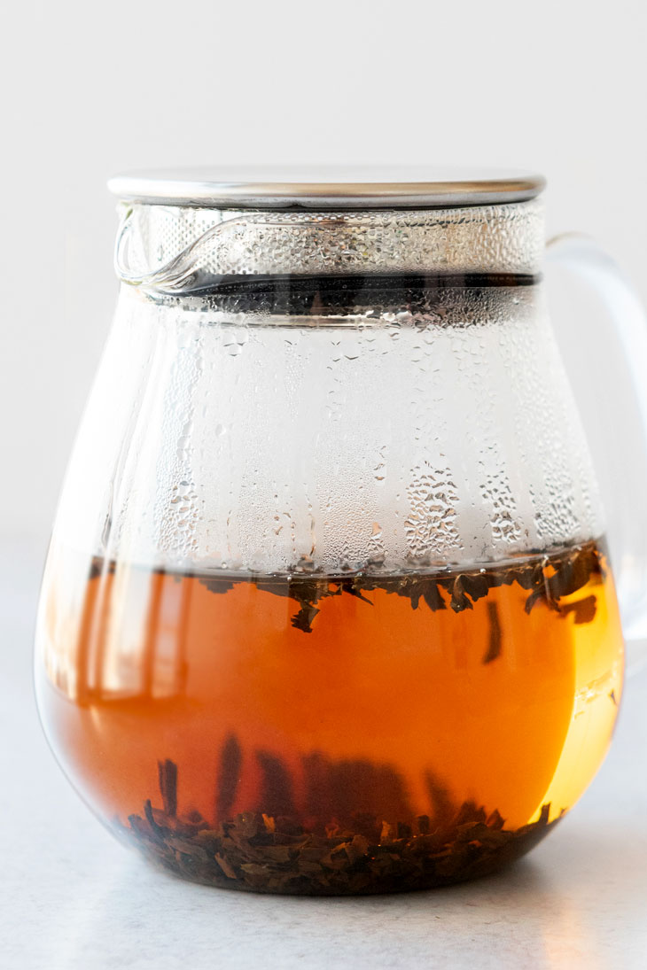 Lapsang souchong hot tea in a glass teapot with tea leaves.