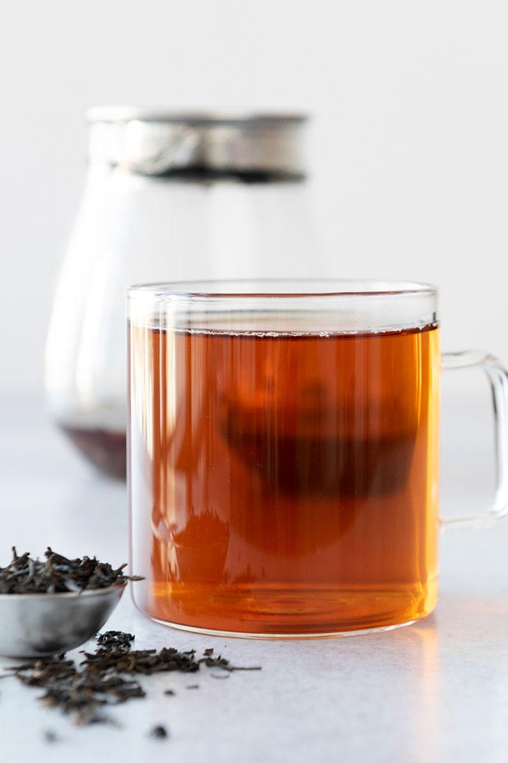Hot lapsang souchong tea in a glass mug.