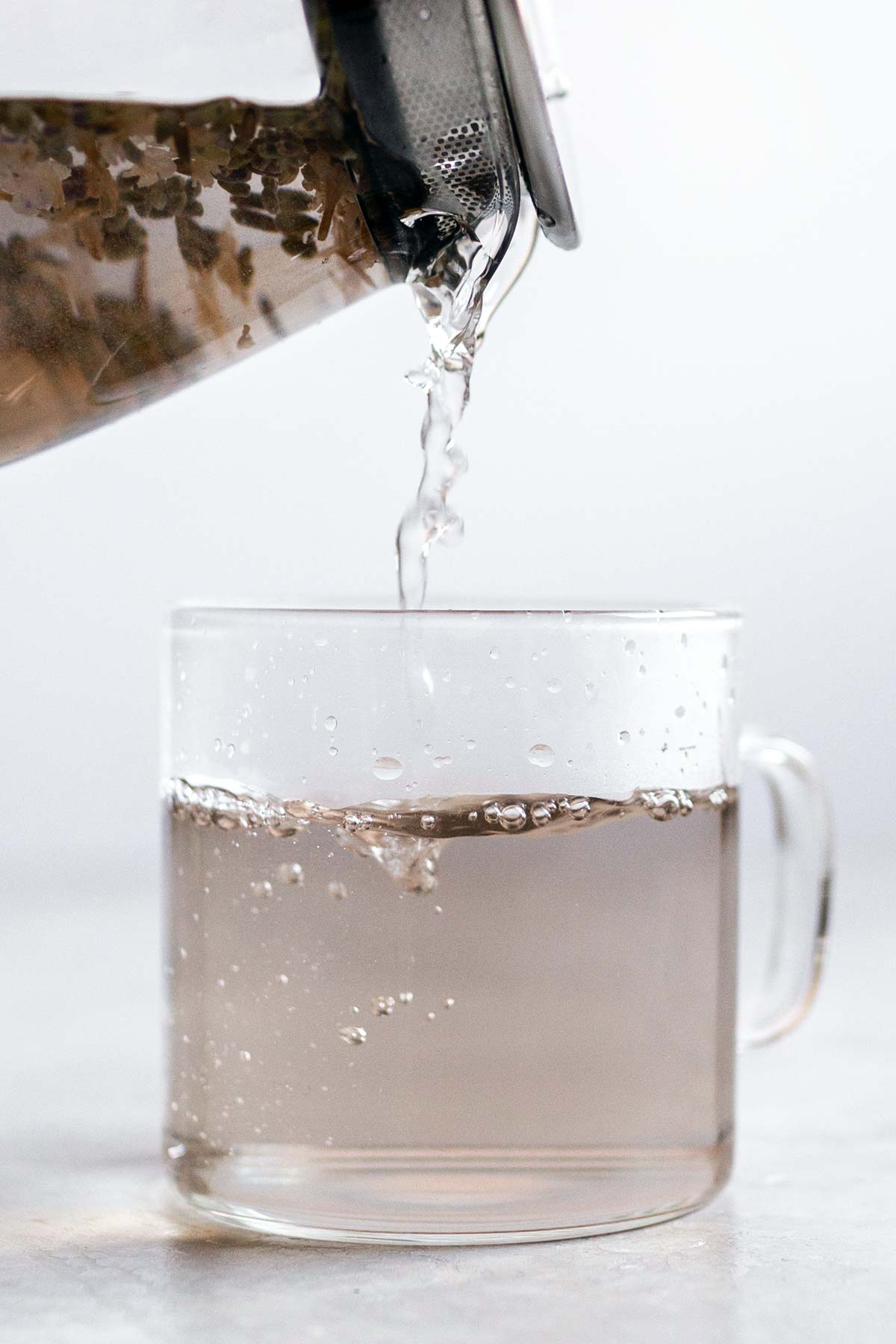 Pouring hot lavender tea in a glass mug.