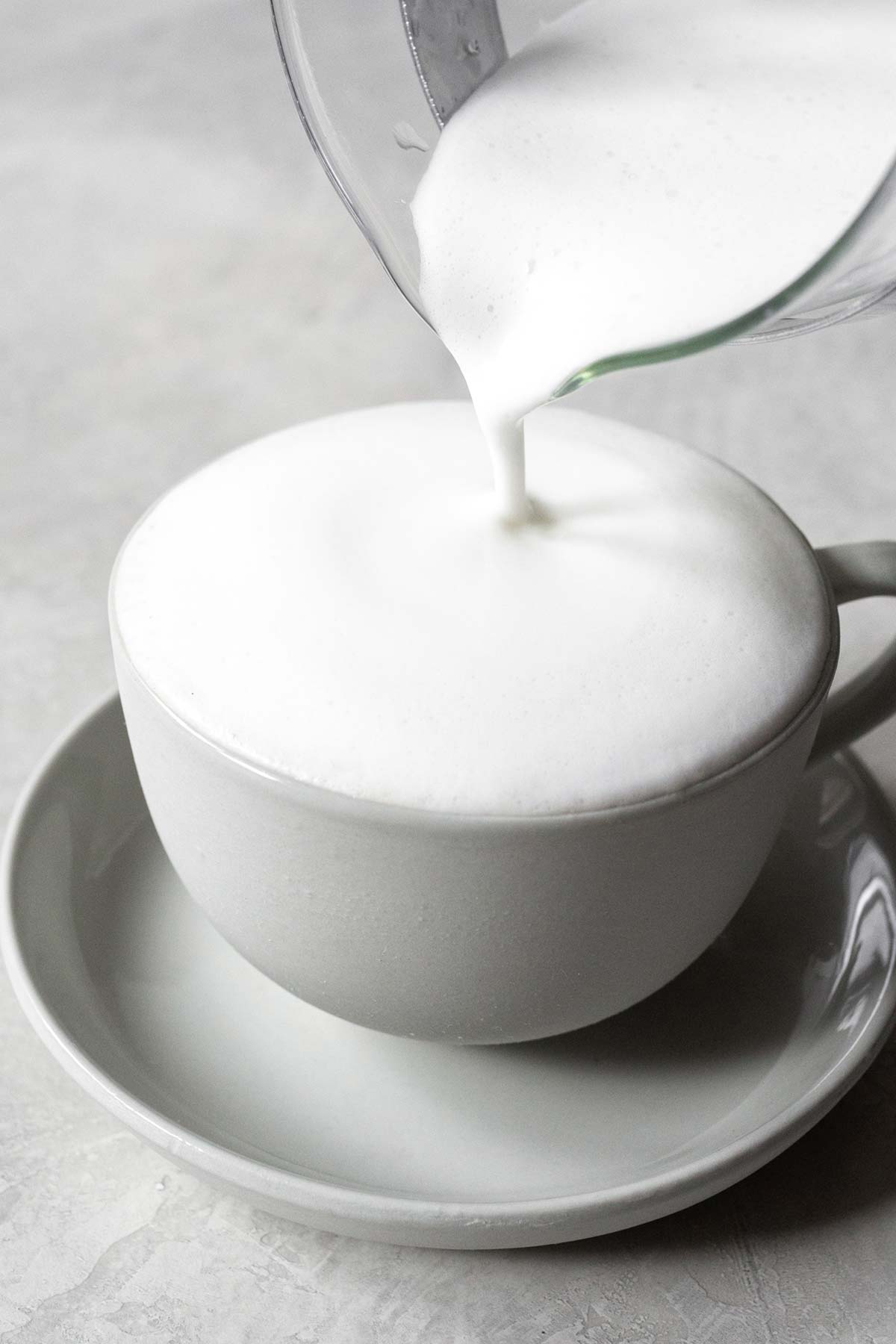 Pouring frothed milk into a cup with Earl Grey tea.