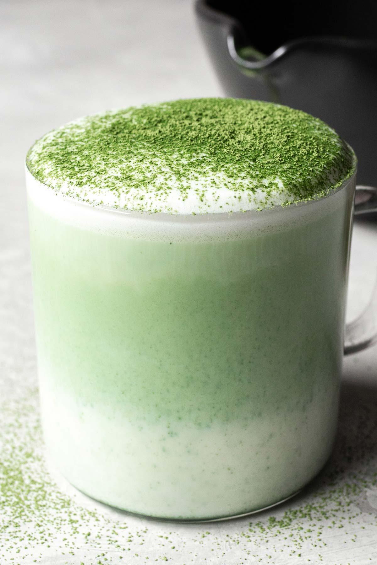 Matcha green tea in a glass mug.