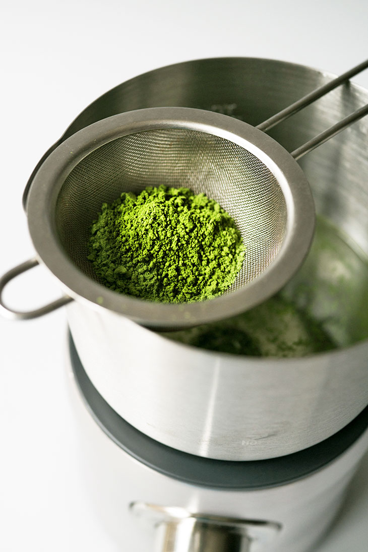 Sifting matcha using a mesh strainer into an electric milk frother.