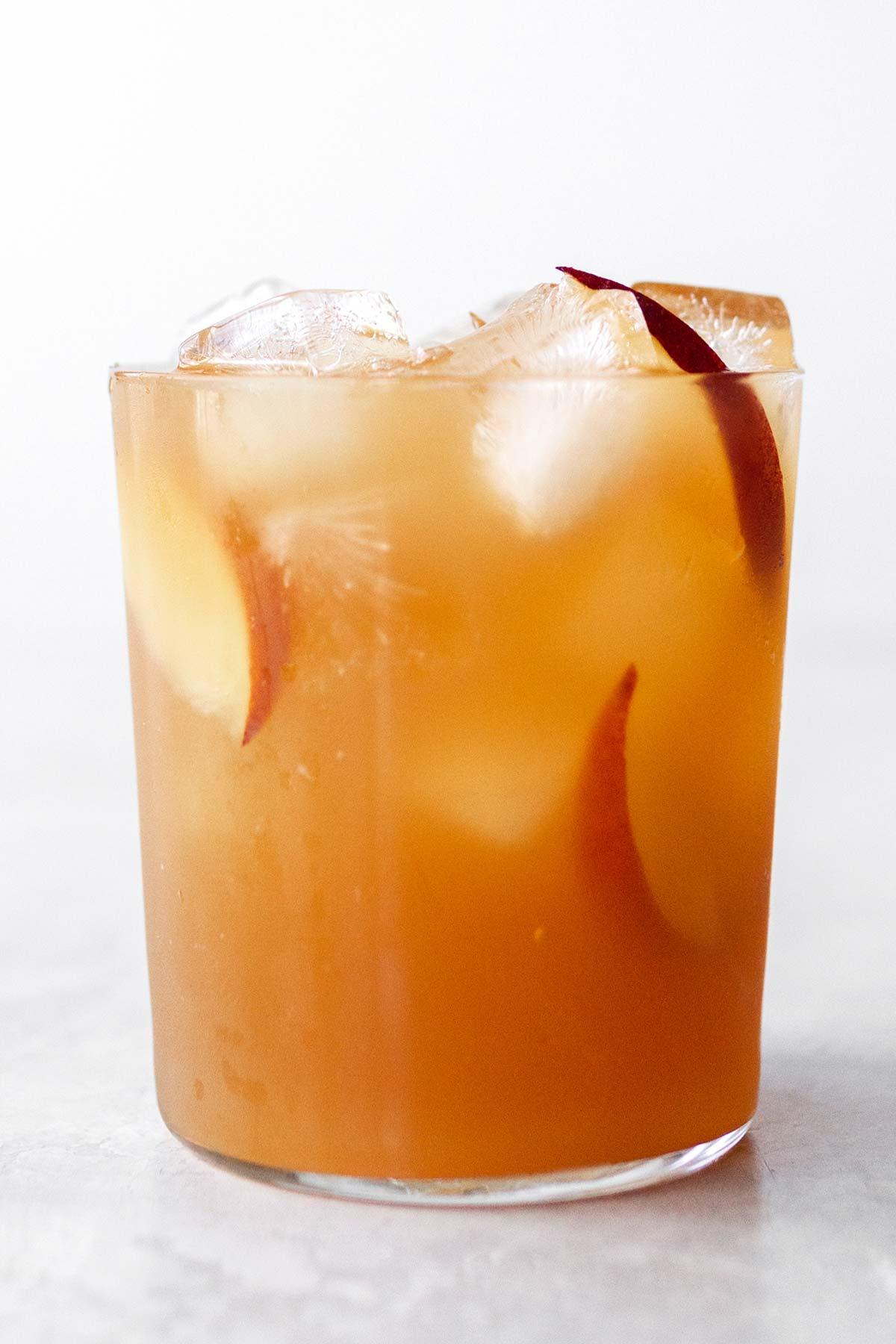 Peach iced tea in a cup with peach slices.