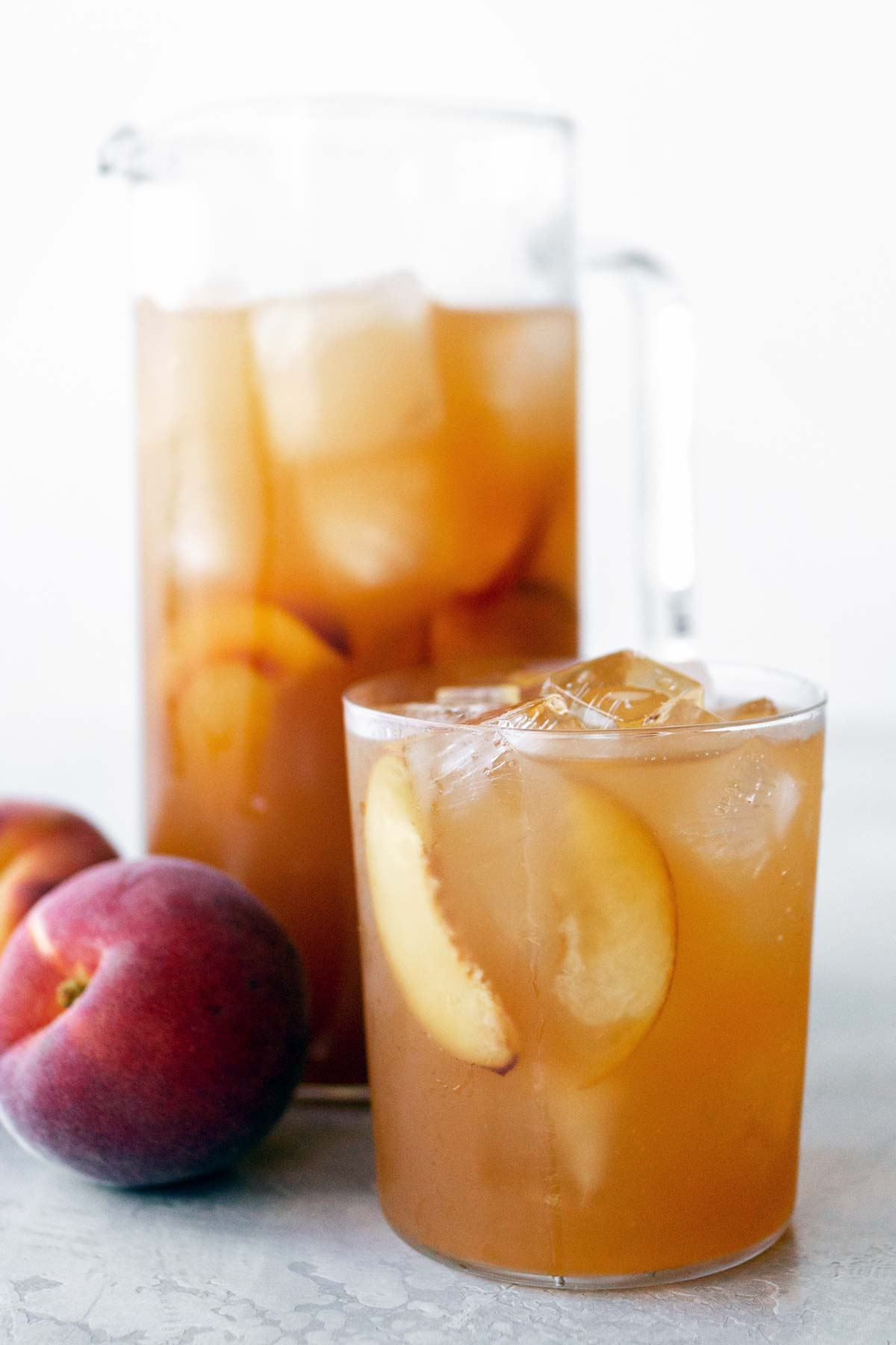 Peach iced tea in a pitcher and in a cup.