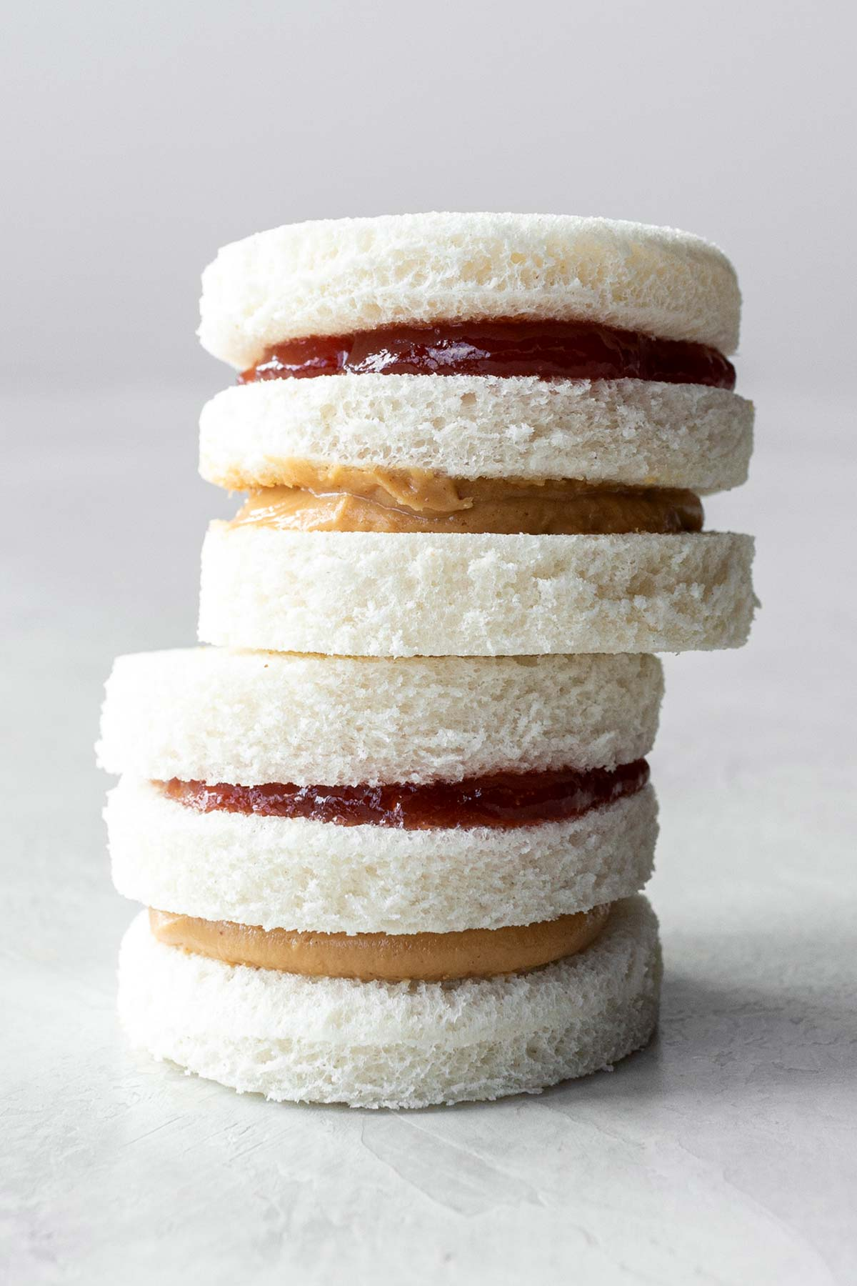 Two peanut butter and jelly tea sandwiches, stacked.