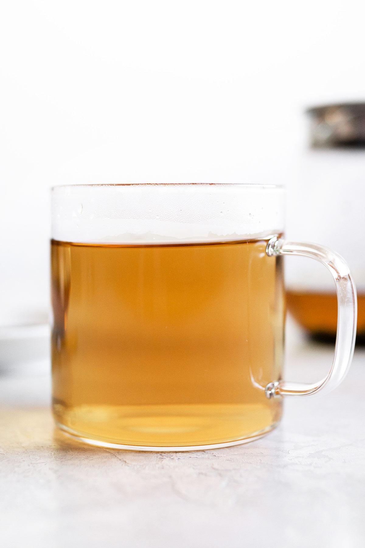Peppermint tea in a glass mug.