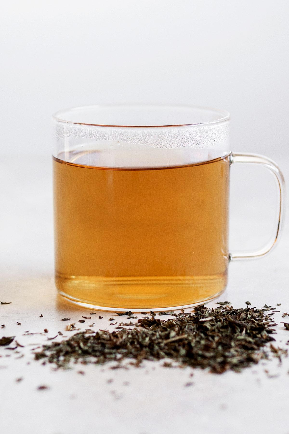 Hot peppermint tea in a glass mug.
