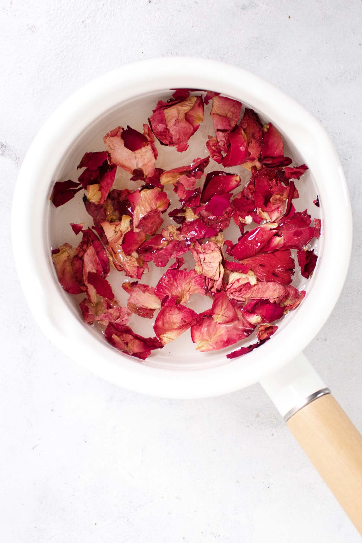 Rose petals in a saucepan with water.