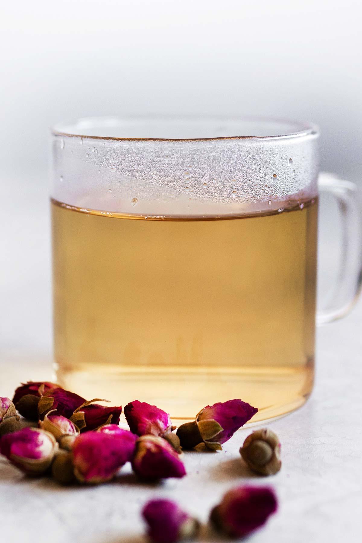 Hot rose tea in a glass mug.