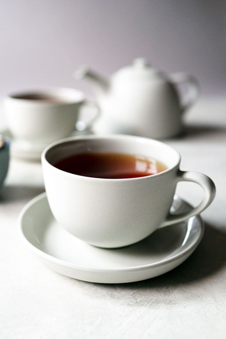 Cup of hot tea with teapot and tea cup in background.