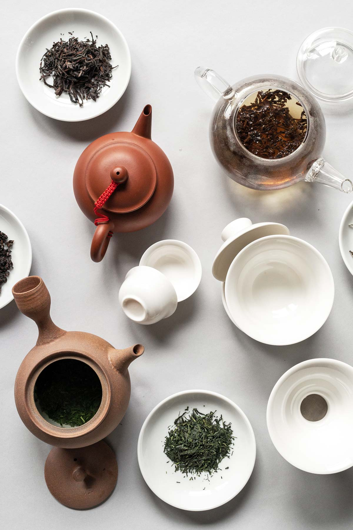 Different teapots and small plates of loose tea.