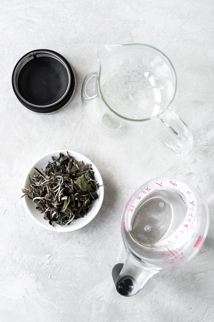 White peony tea ingredients on a surface.